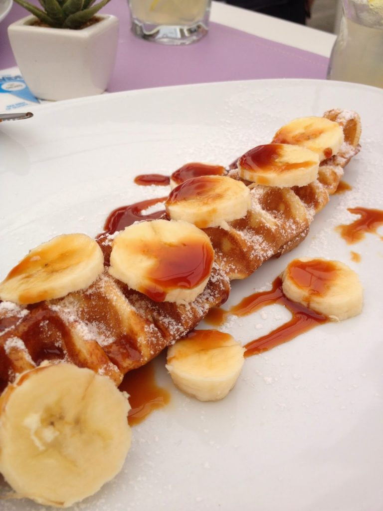 A willy waffle shown with banana and maple syrup